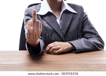 Businesswoman showing middle finger at desk. - stock photo