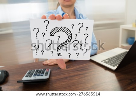 Businesswoman Showing Question Mark Sign On Placard In Office - stock photo