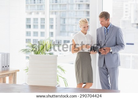 Businesswoman showing something on the tablet computer in an office - stock photo