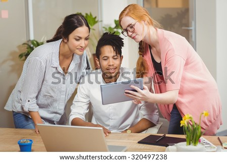 Businesswoman showing something to colleagues on digital tablet at desk during office