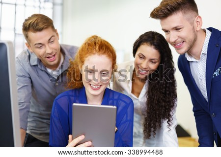 businesswoman showing tablet to colleagues with a smile - stock photo