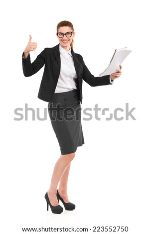 Businesswoman showing thumb up. Elegance woman in black suit posing with a notebook and showing thumb up. Full length studio shot isolated on white. - stock photo
