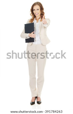 Businesswoman showing thumbs up with clipboard.