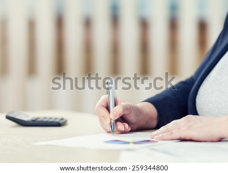 Businesswoman signing a document. Toned photo, shallow depth of field. - stock photo