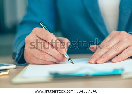 Businesswoman signing business contract agreement at office desk