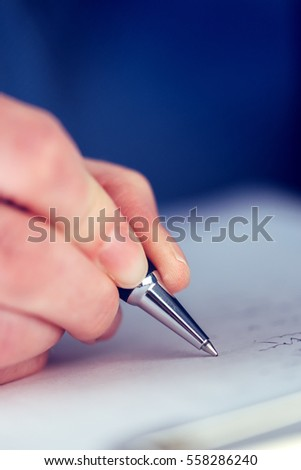 Close Female Hands Writing Signature On Stock Photo