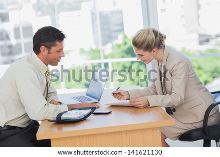 Businesswoman signing contract at interview in office - stock photo