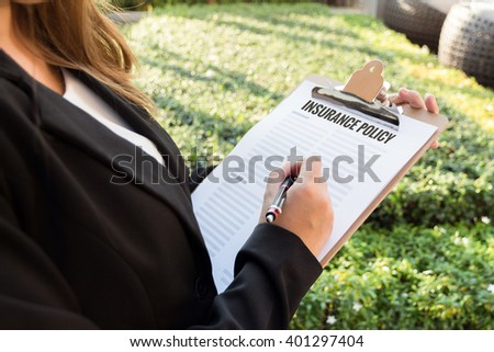 Businesswoman signing insurance policy in the garden. - stock photo