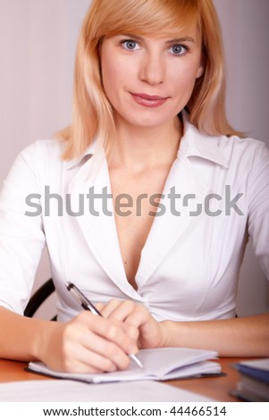 Businesswoman sits at a table in white clothes