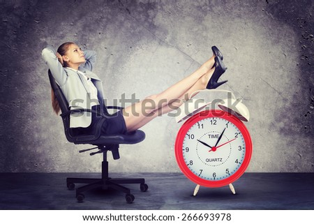 Businesswoman sits in chair, relaxed and put hands behind her head. Put your feet up on big red alarm clock. Concrete background
