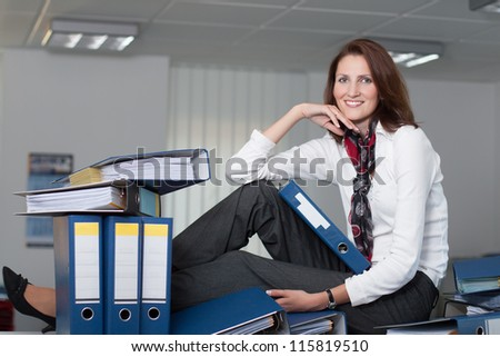 Businesswoman sits on the table surrounded by many files - stock photo