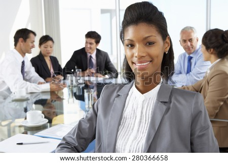 Businesswoman Sitting Around Boardroom Table With Colleagues - stock photo