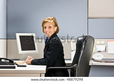 Businesswoman sitting at desk - stock photo