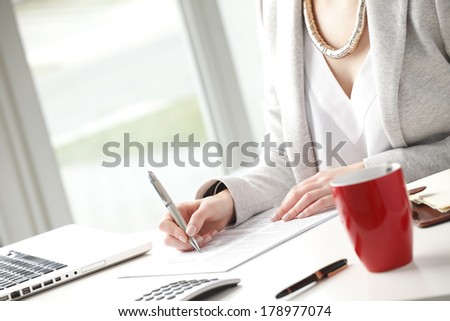 Businesswoman sitting at desk and fill the form.  - stock photo
