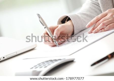 Businesswoman sitting at desk and fill the form.