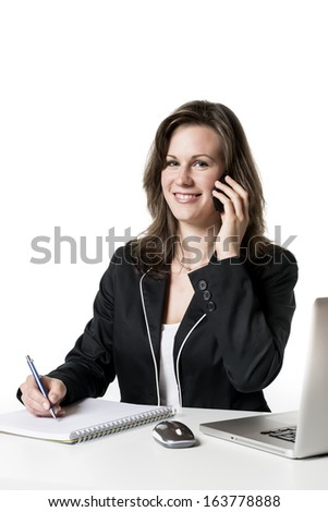 Businesswoman sitting at desk in office and on the phone