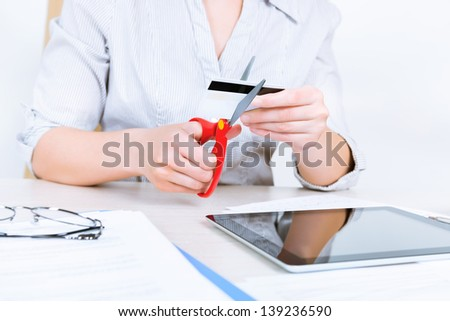 Businesswoman sitting at desk in the office and getting rid of her credit card with the help of scissors after paying back a loan