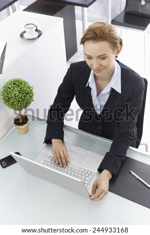 Businesswoman sitting at desk, working with laptop computer. Above view. - stock photo