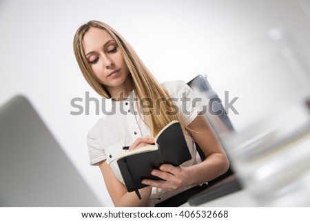 Businesswoman sitting at desk writing in notepad - stock photo