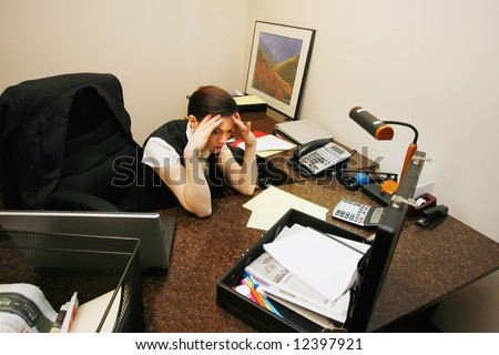 Businesswoman sitting at her desk looking very stressed out with her hands on her temples