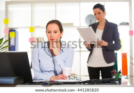 Businesswoman sitting at her desk with colleague on background - stock photo
