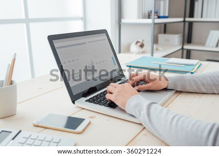 Businesswoman sitting at office desk and typing on a laptop hands close up