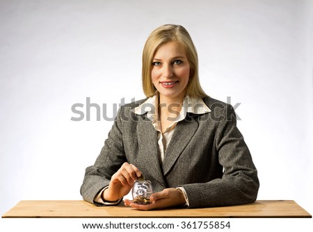 Businesswoman sitting at office table and holding money box.  Business woman with gray jacket putting euro coin into the piggi bank. European finance currency. - stock photo
