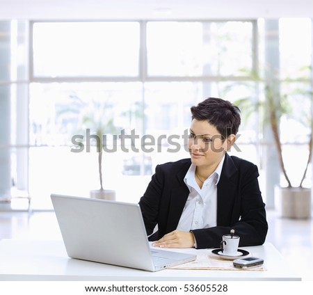 Businesswoman sitting at table in office lobby, using laptop computer, looking at screen. - stock photo