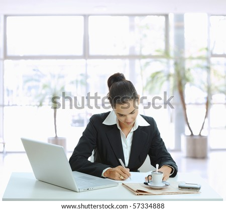 Businesswoman sitting at table in office lobby, writing note on paper. - stock photo