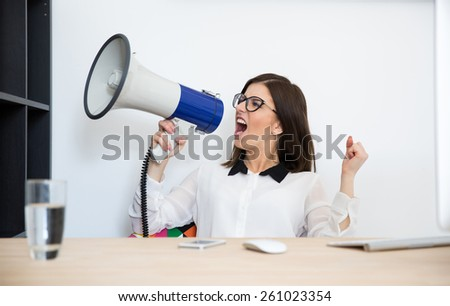Businesswoman sitting at the table and speaking through megaphone - stock photo