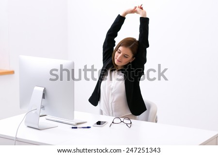 Businesswoman sitting at the table in office and stretching her hands above her head