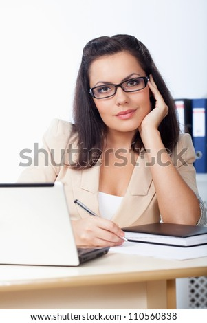 businesswoman sitting behind the desk looking at camera - stock photo