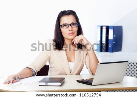businesswoman sitting behind the desk with notebook and papers - stock photo