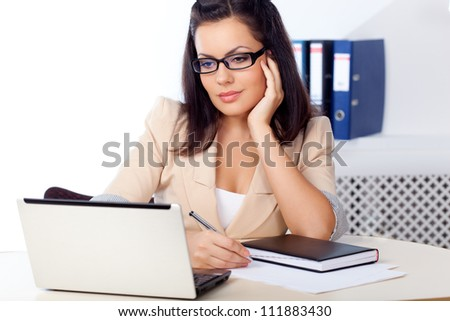 businesswoman sitting behind the desk working  with notebook - stock photo