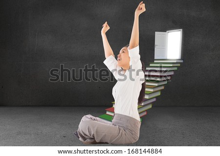 Businesswoman sitting cross legged cheering against steps made from books leading to door in grey room - stock photo