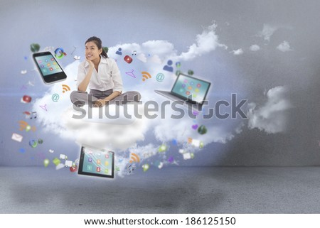 Businesswoman sitting cross legged thinking against clouds in a room - stock photo