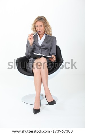 businesswoman sitting cross-legged with a flirtatious look - stock photo
