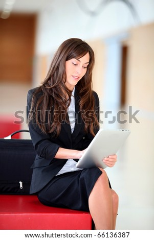 Businesswoman sitting in hall with electronic pad - stock photo