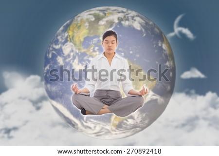 Businesswoman sitting in lotus pose against night sky - stock photo