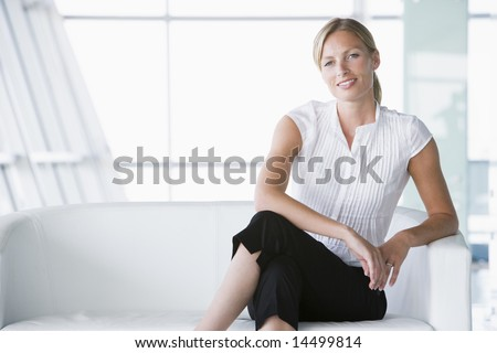 Businesswoman sitting in office lobby smiling - stock photo