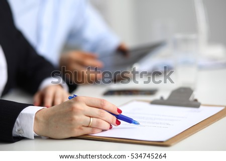 Businesswoman sitting in office, writing on documents.