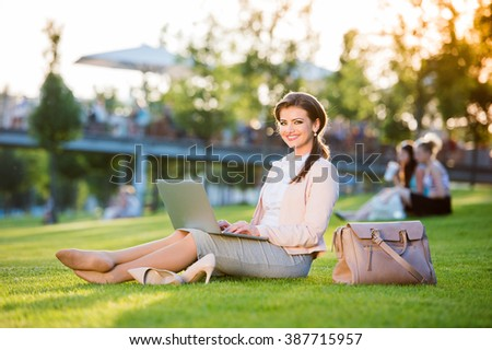 Businesswoman sitting in park working on laptop, sunny summer da