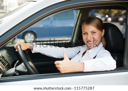 businesswoman sitting in the new car and showing thumbs up