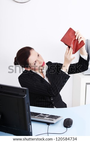 Businesswoman sitting in the office looking at her empty wallet in the office.