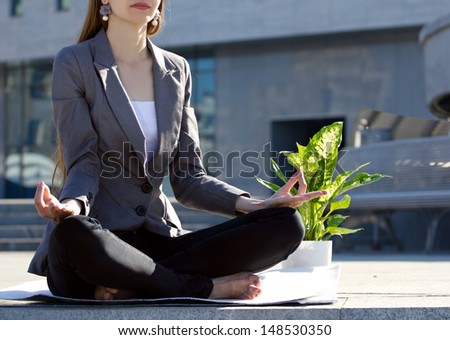 businesswoman sitting in yoga pose, near - flower in pot, on blurred building  background - stock photo