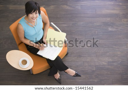 Businesswoman sitting indoors with coffee and folder smiling - stock photo