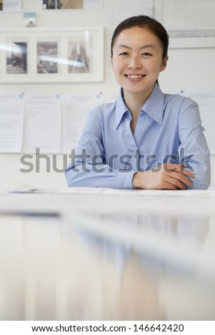 Businesswoman sitting next to the table in the office, portrait - stock photo