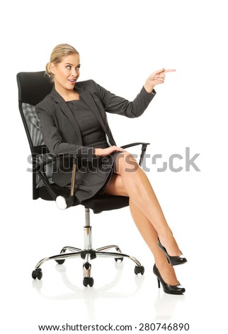 Businesswoman sitting on a chair and showing empty space. - stock photo