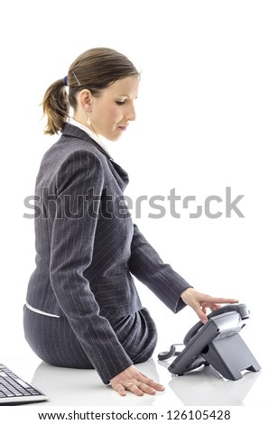Businesswoman sitting on a white office desk just about to pick up the telephone. - stock photo