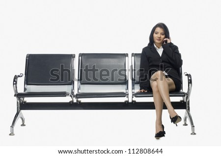 Businesswoman sitting on an armchair and talking on a mobile phone